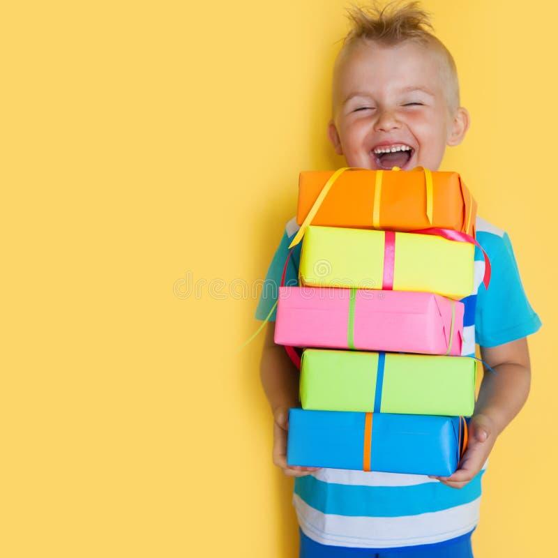 Barnet rymmer ljusa gåvor En pojke med en gåva på en gul fest arkivfoton