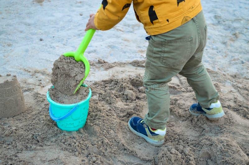 Barnet samlar en stor skyffelsand i en hink och bygger ett torn arkivfoto