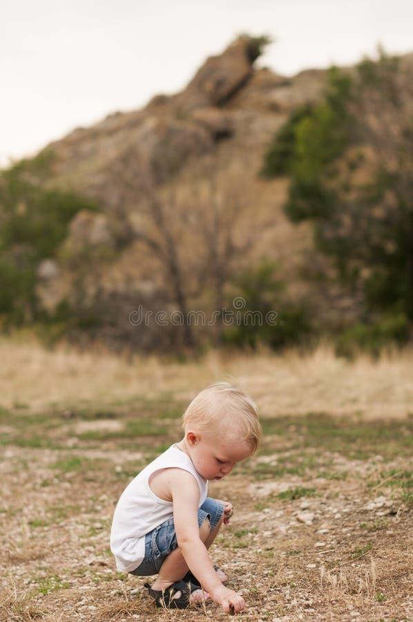 Barnet samlar stenar fotografering för bildbyråer