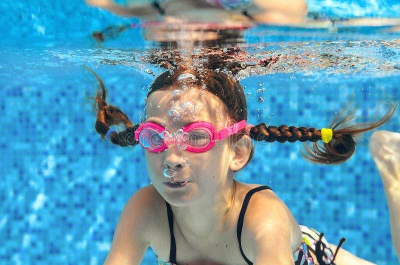 Barnet simmar i den undervattens- pölen, den lyckliga aktiva flickan i skyddsglasögon har gyckel i vatten arkivbilder