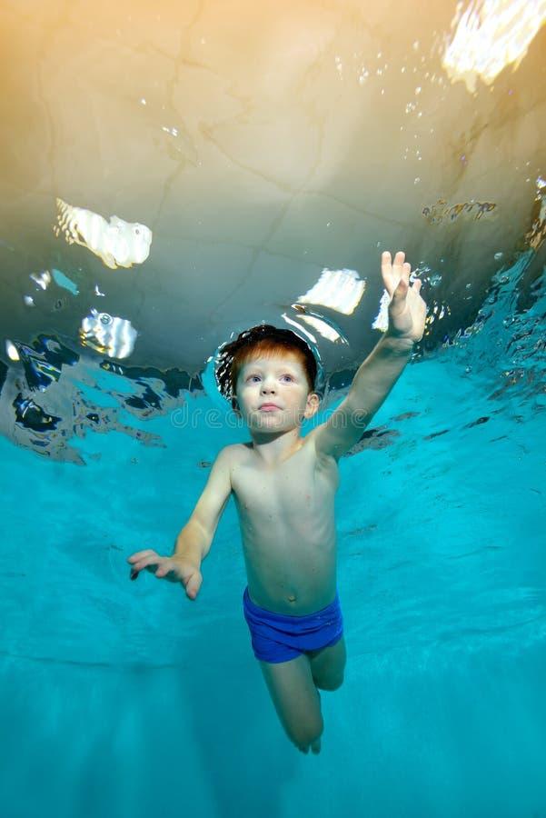 Barnet simmar undervattens- i pölen mot det gula ljuset royaltyfri foto