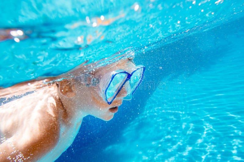 Barnet simmar undervattens- i simbassäng royaltyfri fotografi