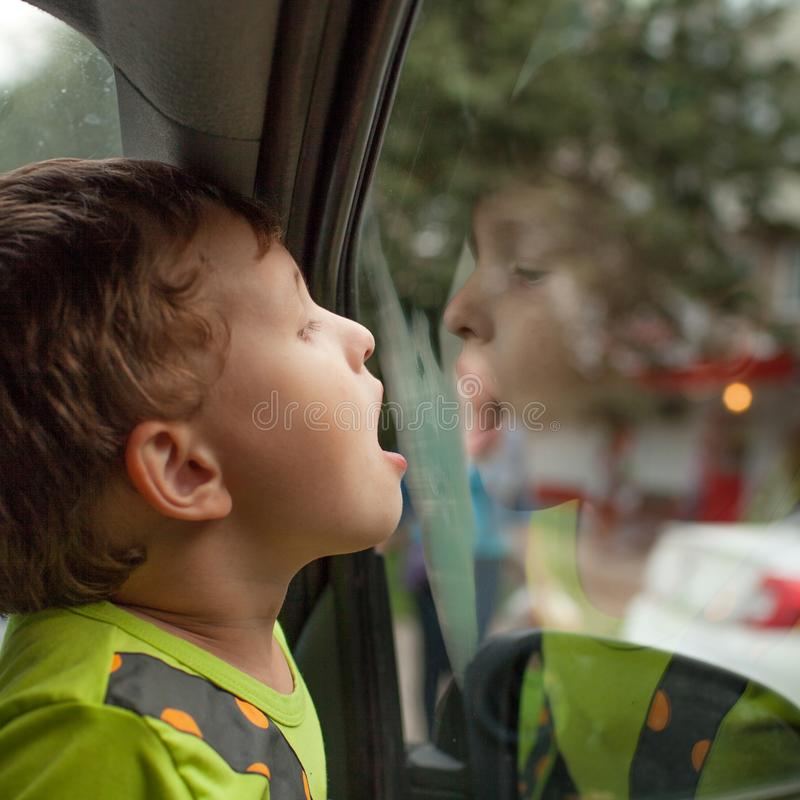 Barnet sitter i bilen bara arkivfoto
