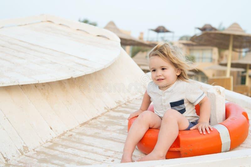 Barnet sitter i cirkelboj på solig dag Pys med livboj på den tropiska stranden Ungen med blont hår har utomhus- gyckel Sommarvaca arkivfoto