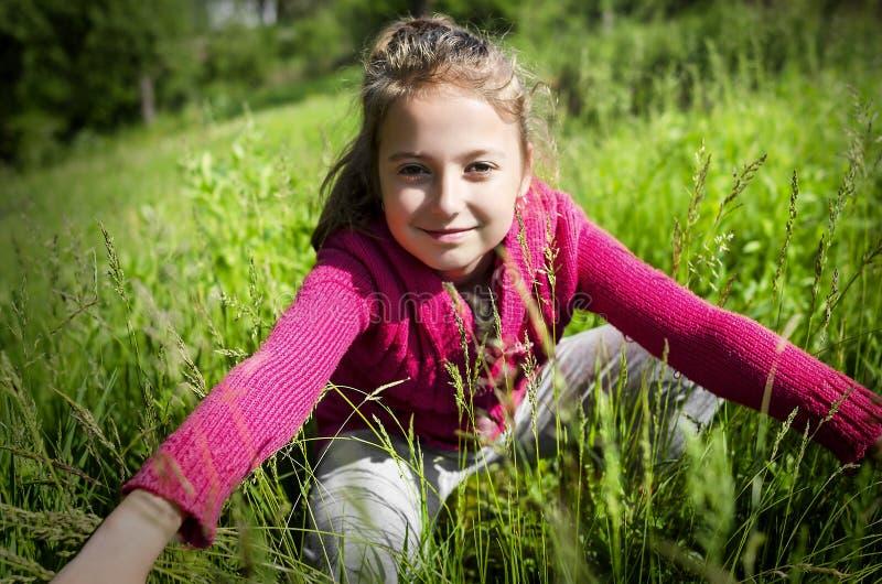 Barnet sitter på gräset arkivbild