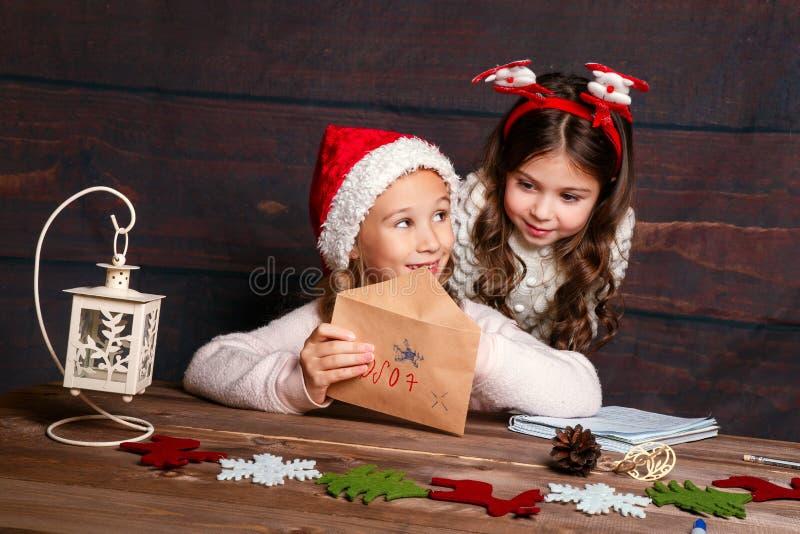 Barnet skrivar brevet till Santa Claus Roliga flickor i jultomtenhatt skrivar brevet till jultomten arkivfoton