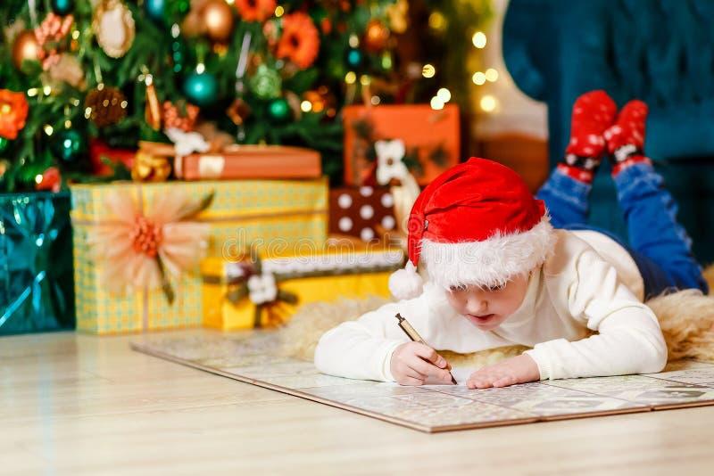 Barnet skrivar ett brev till Santa Claus som ligger på golvet under julgranen fotografering för bildbyråer
