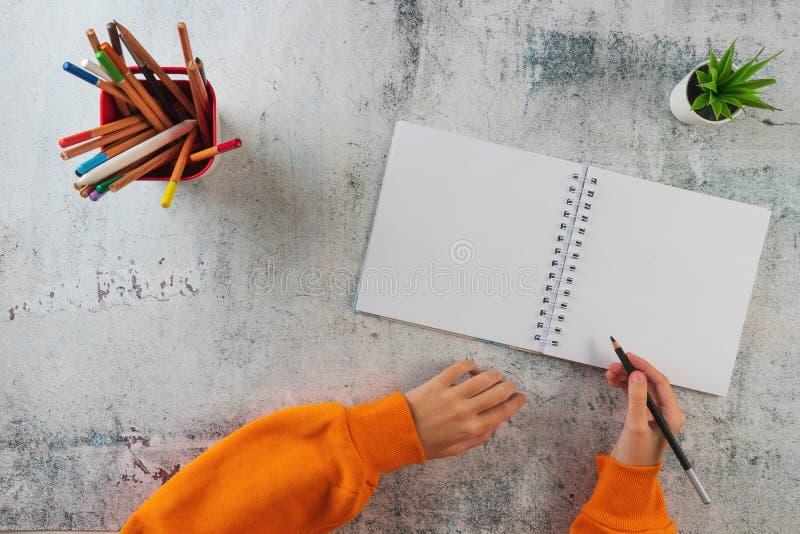 Barnet skriver med blyerts i en anteckningsbok arkivbilder