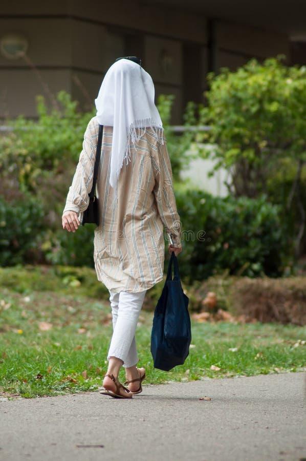 barnet skylde den muslimska kvinnan som går i gatan i t arkivfoton