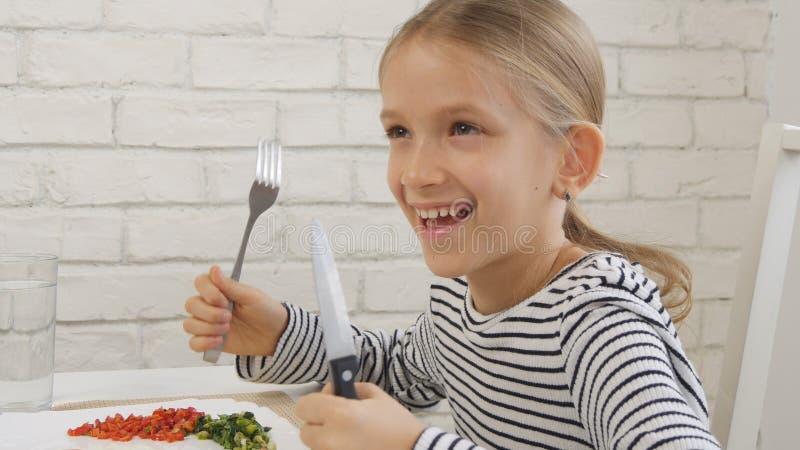 Barnet som äter frukosten i kök, unge äter sunda matägg, flickagrönsaker arkivbild
