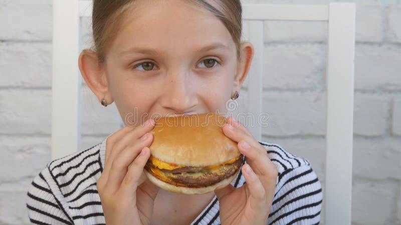 Barnet som äter snabbmat, unge äter hamburgaren i restaurangen, flickan som dricker fruktsaft royaltyfria bilder