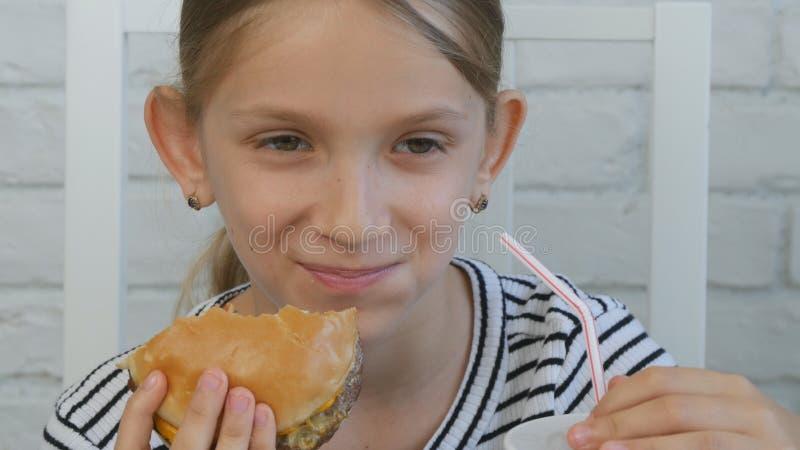 Barnet som äter snabbmat, unge äter hamburgaren i restaurangen, flickan som dricker fruktsaft royaltyfri foto