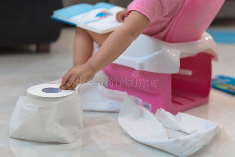 Barnet som använder pottan av henne, medan läsa en bok, når för ett ark av toalettpapper arkivbild