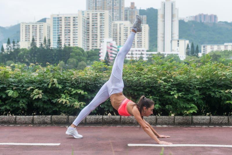 Barnet som den slanka kvinnan som gör yoga dog ner, splittringövning i stad, parkerar på sommardag Kvinnlig idrottsman nen som st arkivfoton