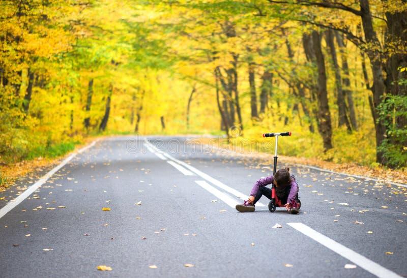 Barnet som faller från hans sparkcykel och anklagar, smärtar royaltyfri foto