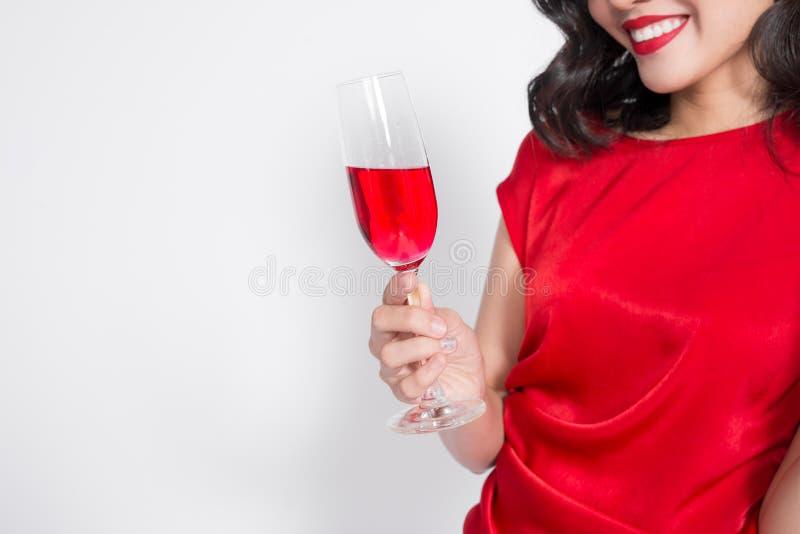 Barnet som firar den härliga asiatiska kvinnan i rött klänninginnehav, segrar royaltyfri foto
