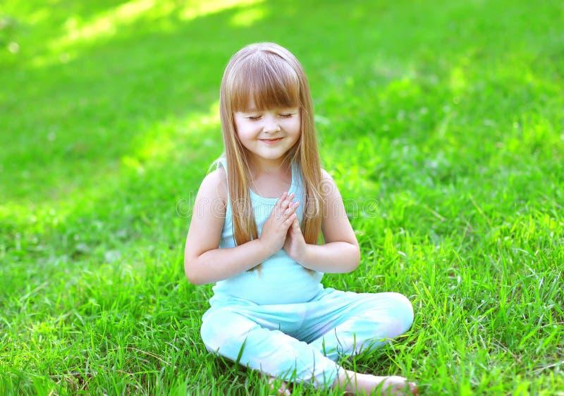 Barnet som gör yoga, övar sammanträde på gräset royaltyfri foto