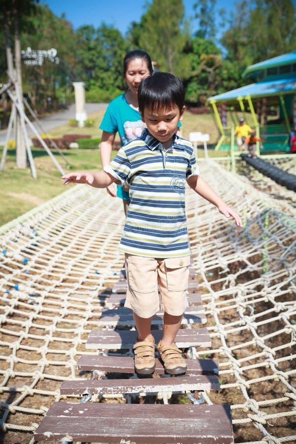 Barnet som har gyckel på lekplatsen, fostrar nära förbi Lycklig asiatisk fami arkivbild