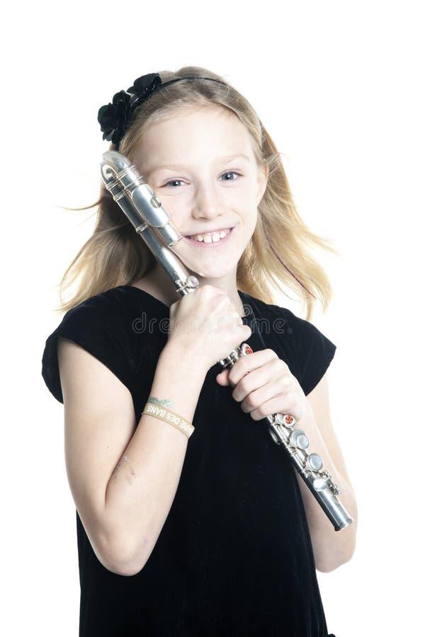 Barnet som ler blonda flickahåll, blåser flöjt i studio royaltyfria bilder