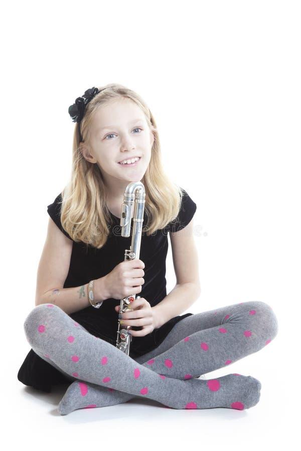 Barnet som ler blonda flickahåll, blåser flöjt i studion som ner sitter fotografering för bildbyråer