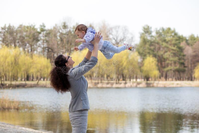 Barnet som modern kastar behandla som ett barn upp, i himlen, på solig dag arkivbild