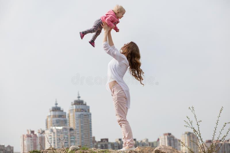 Barnet som modern kastar behandla som ett barn upp, i himlen, på solig dag royaltyfria foton