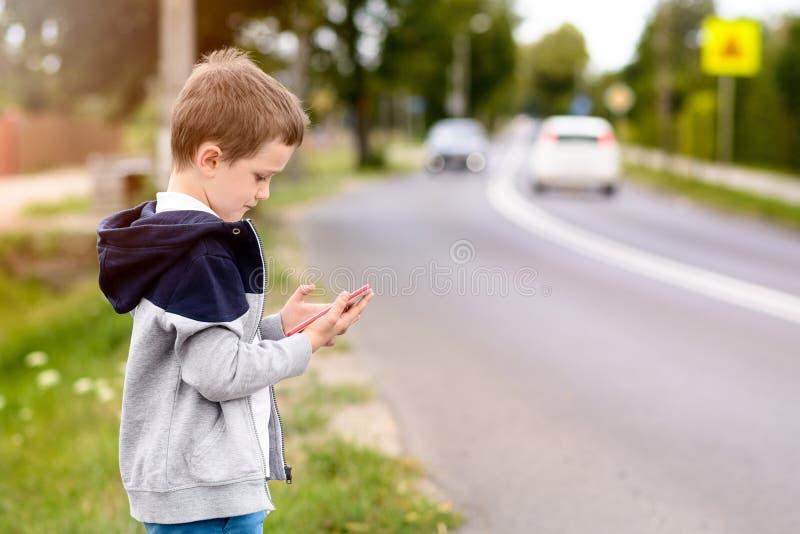 Barnet som spelar mobilen, spelar på smartphonen på gatan royaltyfria bilder