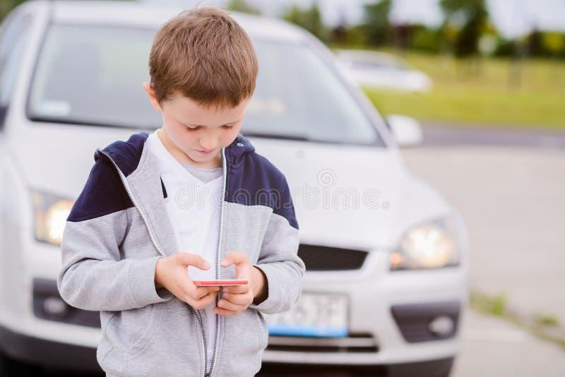 Barnet som spelar mobilen, spelar på smartphonen på gatan arkivfoton