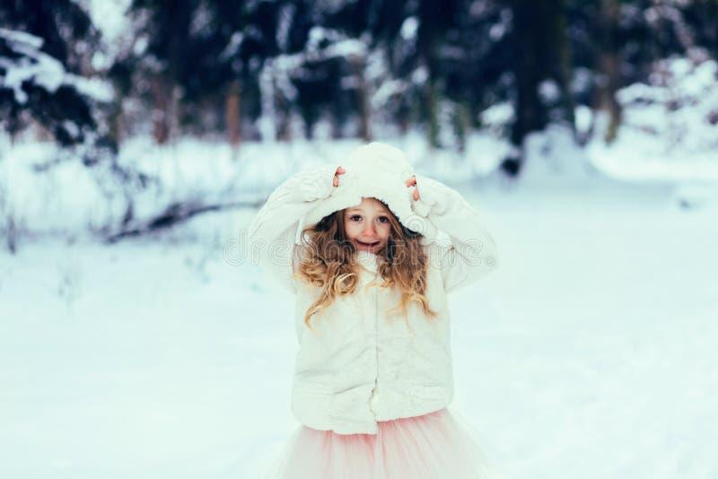 Barnet som spelar på en vinter, går arkivfoton