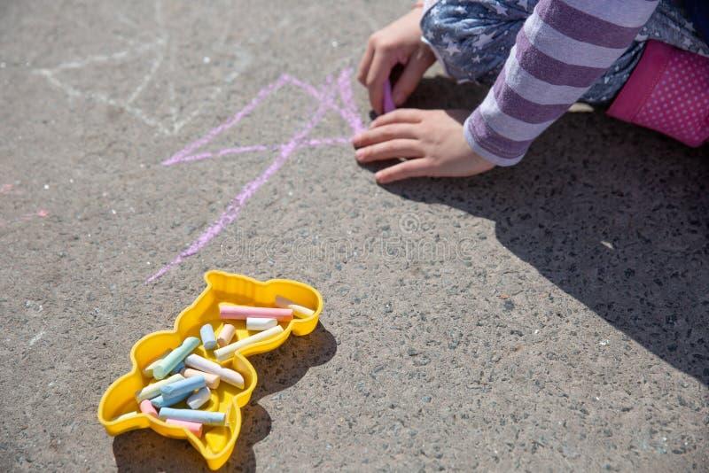 Barnet som tecknar en krita på asfalt arkivfoto