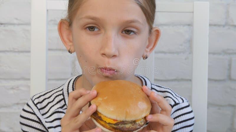 Barnet som ?ter snabbmat, unge ?ter hamburgaren i restaurangen, flickan som dricker fruktsaft arkivfoto