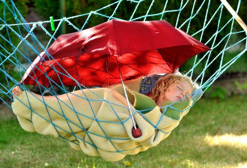 Barnet sovar i en hängmatta. arkivfoto