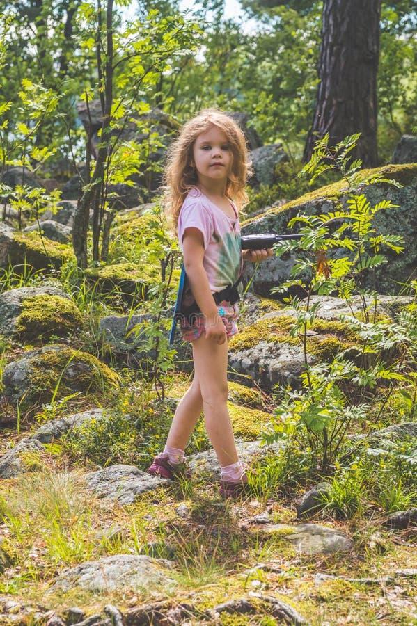 Barnet spanar i skogen med walkie-talkie arkivbilder