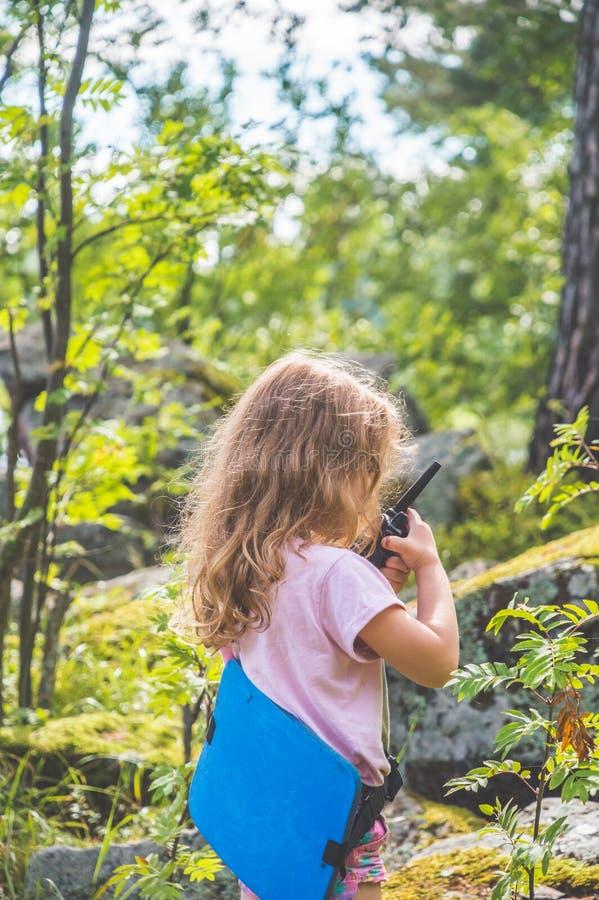 Barnet spanar i skogen med walkie-talkie royaltyfri bild