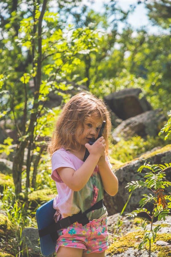 Barnet spanar i skogen med walkie-talkie arkivfoton