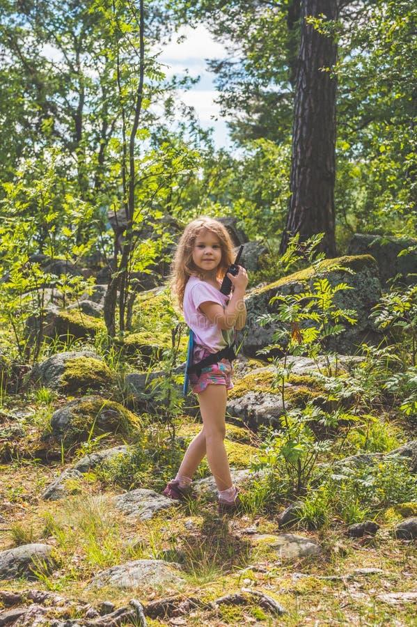 Barnet spanar i skogen med walkie-talkie arkivbild