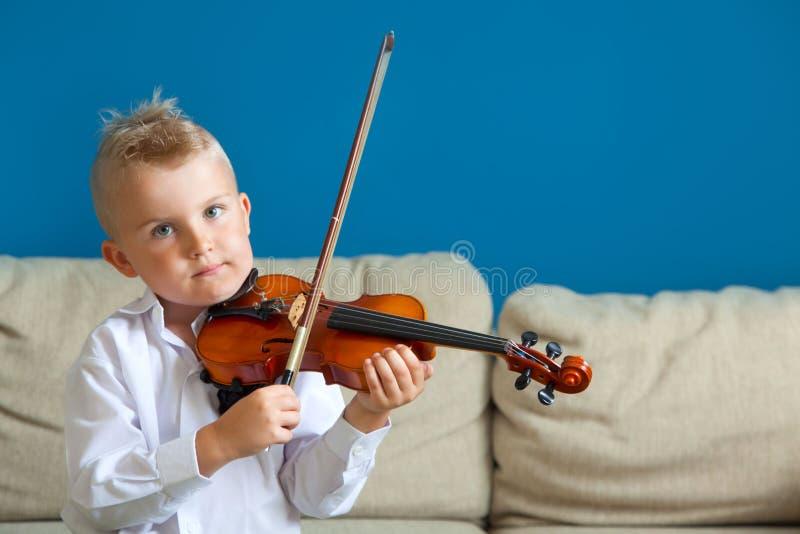 Barnet spelar fiolen Pojke som studerar musik royaltyfri fotografi