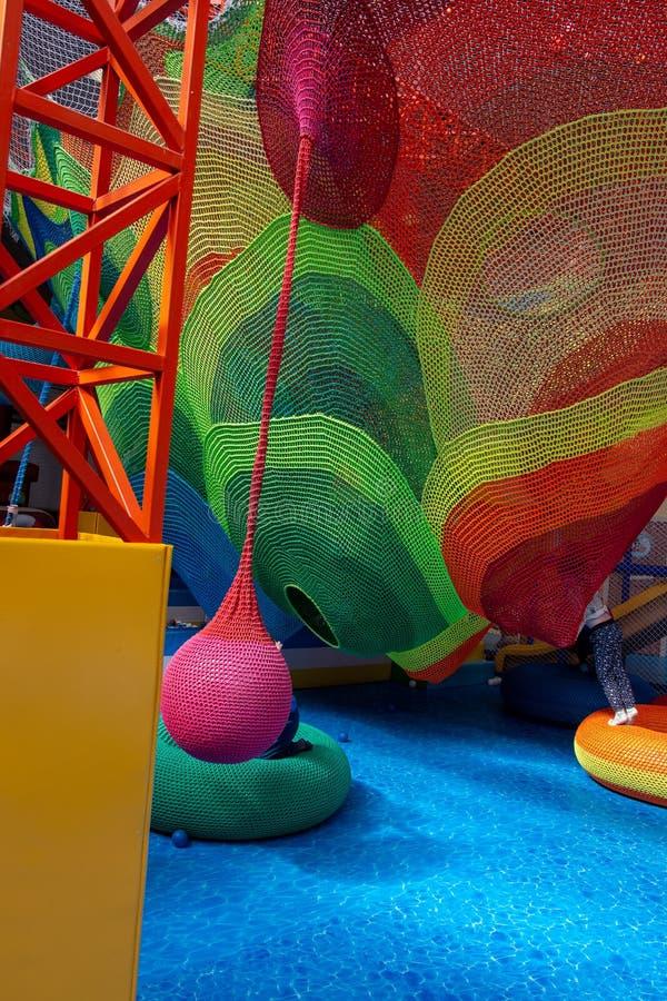 Barnet spelar lyckligt p? lekplatsen royaltyfria bilder
