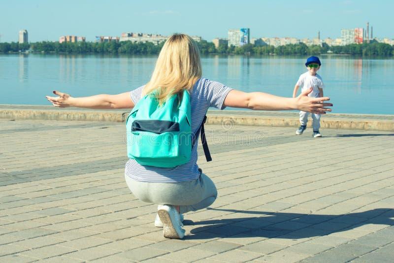 Barnet spelar med hans moder Pojken kör för att krama hans älskade moder royaltyfria bilder