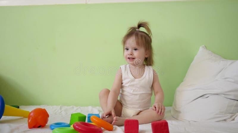 Barnet spelar med mångfärgade kuber på en vit säng och kastar dem till hans moder Bildande leksaker för förträning och arkivfoton