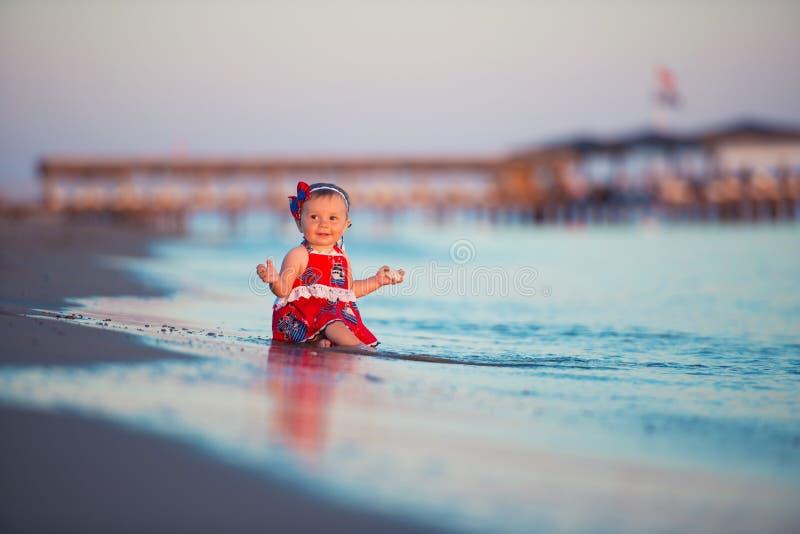 Barnet spelar på sanden på kusten på solnedgångtid royaltyfria bilder