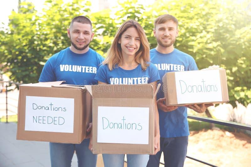 Barnet ställa upp som frivillig innehavaskar med donationer för fattigt folk royaltyfri bild