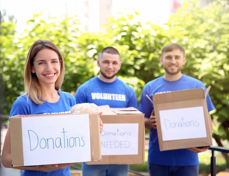 Barnet ställa upp som frivillig innehavaskar med donationer för fattigt folk royaltyfri foto