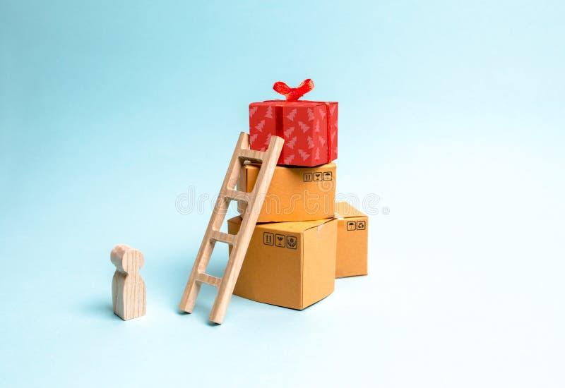 Barnet står nära en gåvaask på en hög av askar Begreppet av att finna den perfekta gåvan Inskränkt erbjudandeköp en gåva i rätt t royaltyfri foto