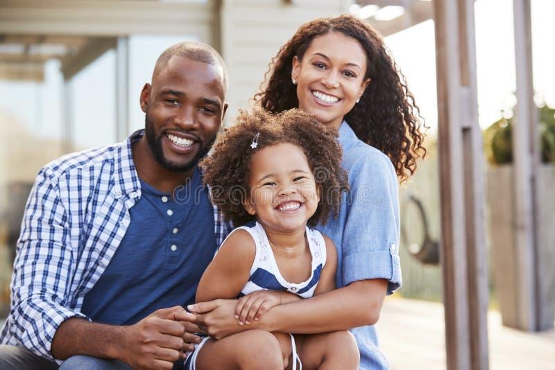 Barnet svärtar familjen som utomhus omfamnar och ler på kameran royaltyfria foton
