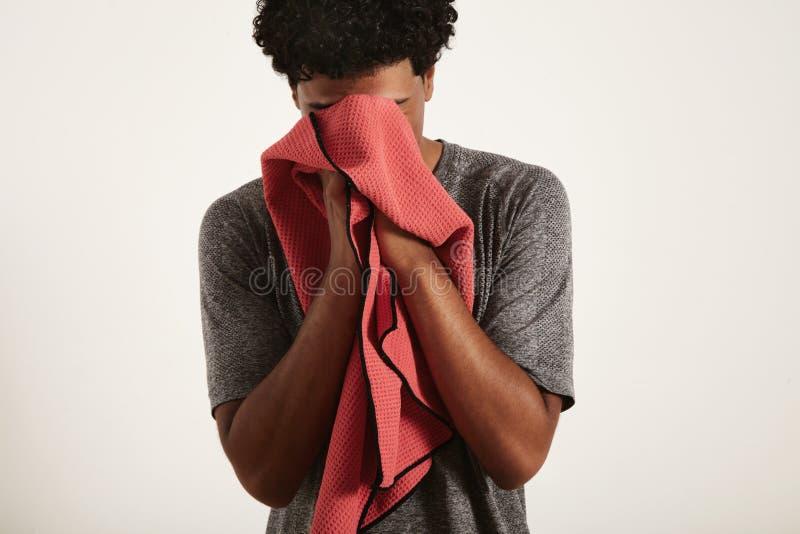 Barnet svärtar idrottsmannen som torkar hans framsida med en handduk arkivfoton
