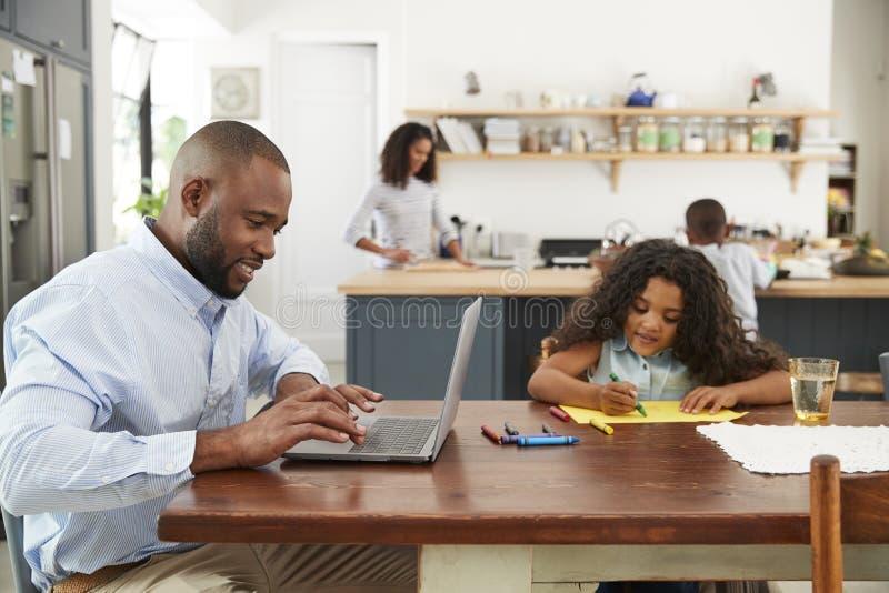Barnet svärtar upptaget arbete för familjen i deras kök royaltyfria foton