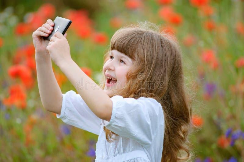 Barnet tar fotoet med mobiltelefonkameran som är utomhus- i natur royaltyfria foton