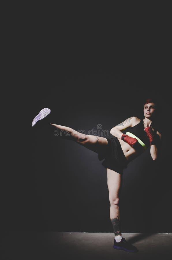 Barnet tatuerade kvinnaboxareboxning med benet arkivbild