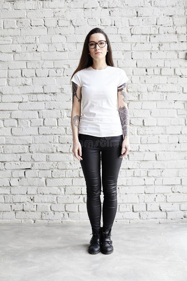 Barnet tatuerade kvinnan som bär den tomma t-skjortan som framme står av tegelstenväggen i vind royaltyfri fotografi